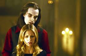 "In Season 5 Episode 1 ""Buffy vs Dracula"" what color pants is Buffy wearing when she first meets Dracula in the cemetary?"
