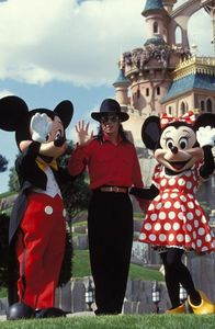 Who is this man in the photograph with Mickey and Minnie