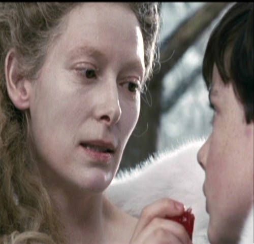 Jadis looks at Edmund eating the Turkish Delight.