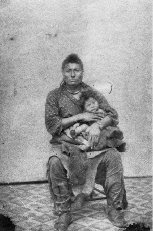 Native American (Pawnee) man holding a small child - Hamilton - 1867